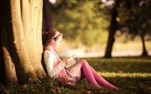 niña-leyendo-apoyada-en-un-arbol
