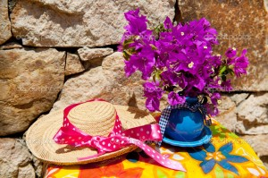 Bouquet Bougainvillea in blue vase with summer straw hat
