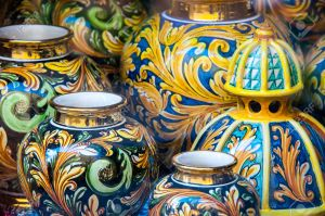 View of some typical colored ceramic vases from Caltagirone behind the window of a shop