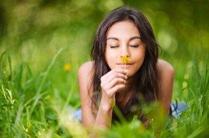 Mujer-oliendo-una-flor-teniendo-recuerdos