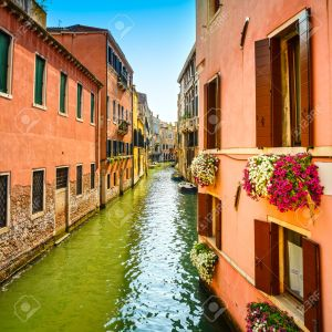 Venice cityscape, Cannaregio water canal, flowers, building and boats. Italy, Europe.